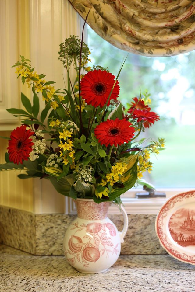 Red and yellow flowers in an earthenware pitcher in front of a kitchen window